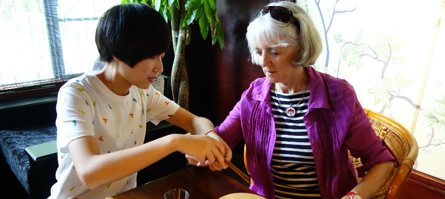 tour guide teaching customer to use chopsticks