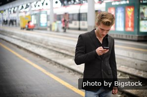 young man on train platform with cell phone