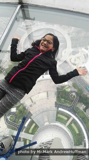 A brave guest on a glass-bottomed sightseeing floor at 259 meters