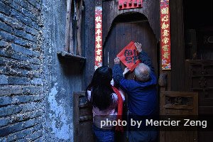 Houses in China are decorated with red couplets and paintings during Chinese New Year