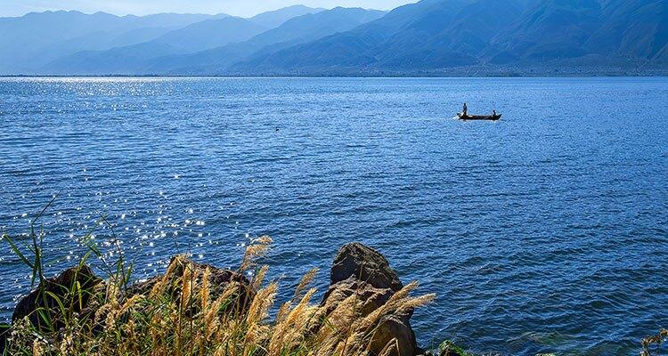 a fisherman on the blue lake
