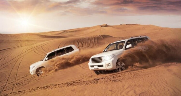two cars driving in the desert in Zhongwei