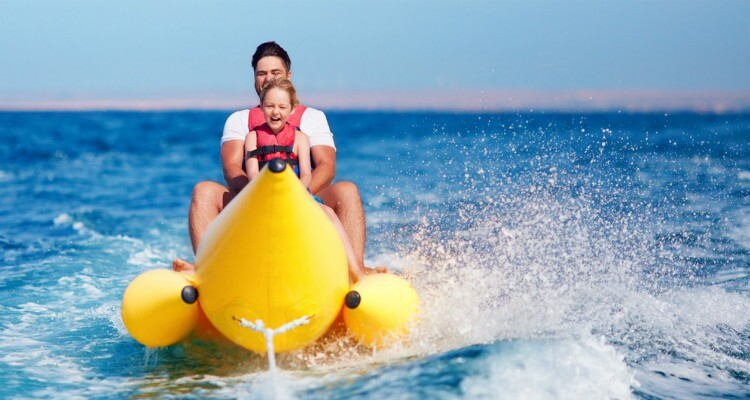 father and son on a banana boat