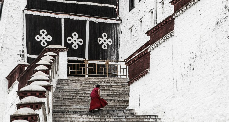 a monk with red dress on Potala Palace